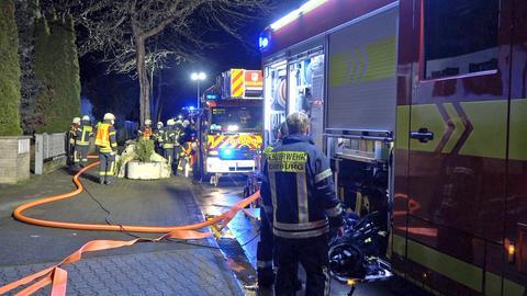 Feuerwehrleute und Feuerwehrwagen mit Schlauch