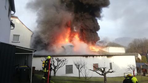 Über einem brennenden Gebäude stehen dichte schwarze Rauchwolken, davor stehen zwei Feuerwehrleute