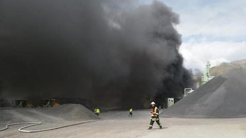 Schwarzer Rauch steht über dem Firmengelände.