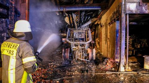 Ausgebrannte Landmaschine in einer Halle, Feuerwehrmann löscht