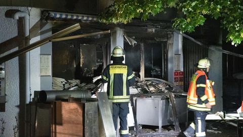Ausgebranntes Restaurant und Feuerwehrleute im Einsatz
