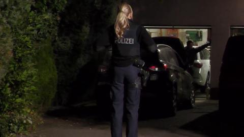 Beschädigtes Auto steht vor der Garage, Foto bei Dunkelheit