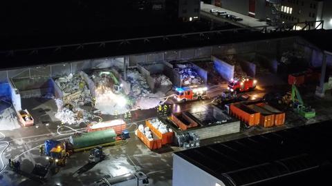 Ein Firmengelände mit Ablageplätzen für Müll aus der Vogelperspektive, auf dem Feuerwehrautos stehen