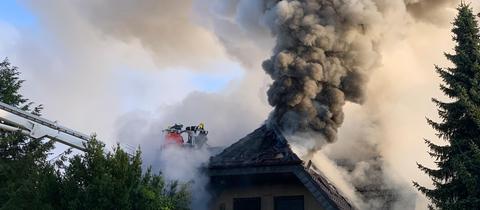 Feuerwehrleute versuchen den Brand im Obergeschoss zu löschen