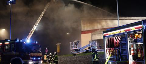 Feuerwehrleute mit Einsatzfahrzeuge beim Löschen von brennender Halle