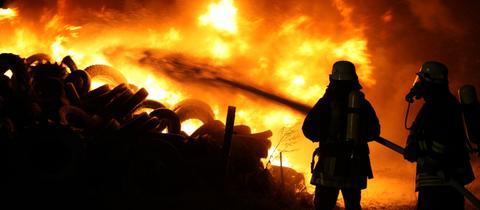 Zwei Feuerwehrmänner mit Gasmasken vor einem brennenden Reifenstapel