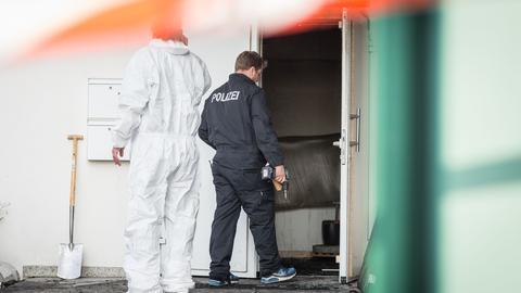 Ermittler der Polizei sichern am Brandort Spuren.