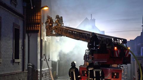 Feuerwehrlaute löschen einen Brand von einer Drehleiter