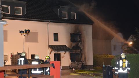 Feuerwehrleute löschen an einem verrußten Haus.