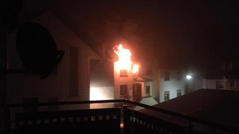 Ein Foto aus der Nachbarschaft zeigt das brennende Haus.