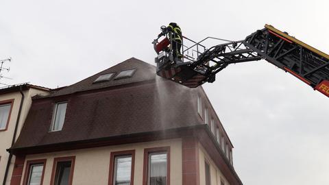 Feuerwehrleute stehen auf einer Drehleiter und löschen.