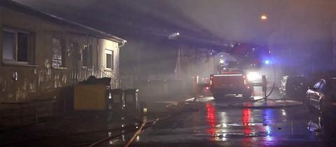 Feuerwehr löscht den Brand einer Lagerhalle, alles ist stark verraucht.