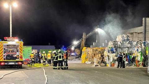 Feuerwehrleute löschen mit Wasser zusammengepackten Abfall.