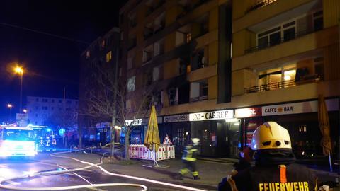 """Ein Feuerwehrmann blickt in der Nacht auf ein mehrstöckiges, hellerleuchtetes Wohnhaus. Auf seinem Rücken ist die Aufschrift """"Feuerwehr Kassel"""" zu lesen. Auf dem Boden sind Schläuche ausgerollt."""