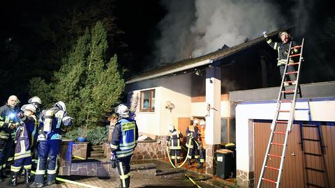 Feuerwehrleute vor einem brennenden Haus