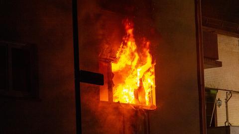 Flammen schlagen aus einem Fenster im Obergeschoss.