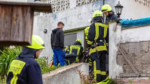 Einsatzkräfte verschaffen sich Zutritt zu dem brennenden Haus.