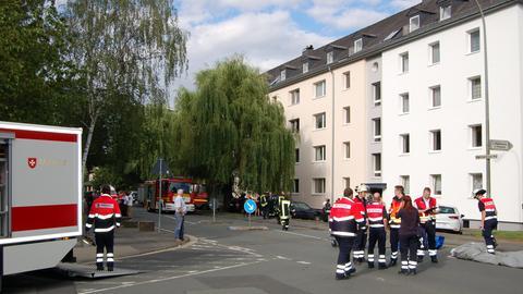 Feuerwehrleute stehen vor dem Mehrfamilienhaus