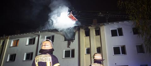 Feuerwehrmänner vor dem brennenden Haus