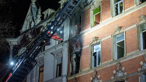 Feuerwehrleute klettern mit einem Kran ins Innere des Gebäudes.