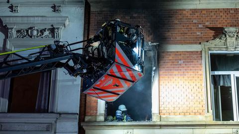 Feuerwehrleute klettern über eine Drehleiter ins Innere des Hauses in Wiesbaden, wo es in der Nacht zum Donnerstag brannte
