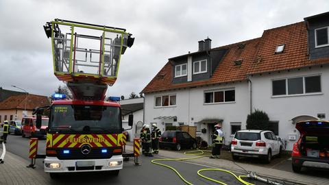 Feuerwehrleute vor einem Reihenhaus