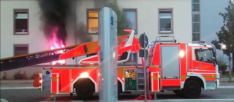 Ein Feuerwehrwagen parkt vor einem Fenster der Offenbacher Psychiatrie aus dem Flammen schlagen.