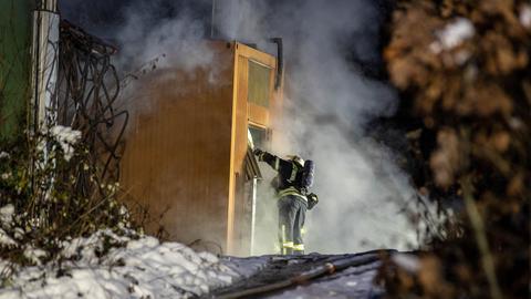 Ein Feuerwehrmann beim von dichten, schwarzen Rauch umgebenem Funkmast bei Wiesbaden