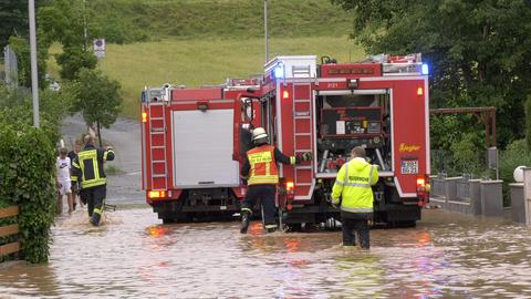 Feuerwehrleute waten durch das Wasser
