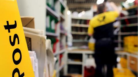 Ein Briefträger in einem Briefverteilzentrum.