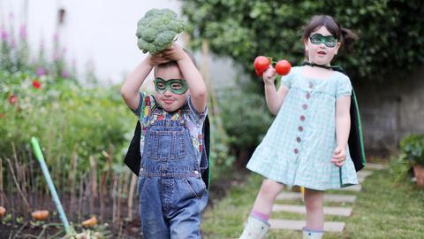 Verkleidete Kinder mit gemüse in der Hand
