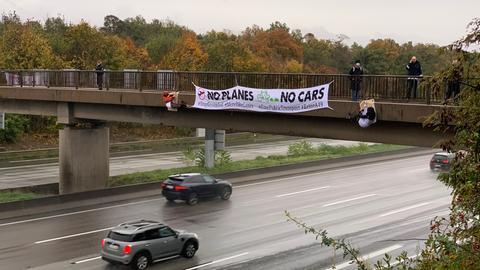 Aktivisten seilen sich von einer Brücke auf die A5 ab.