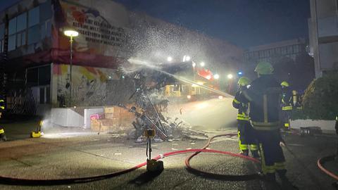 Feuerwehrleute löschen einen Haufen brennender Bücher, im Hintergrund ist eine Baumaschine mit großer Schaufel zu sehen.