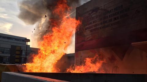 Meterhohe Flammen lodern im Halbdunkel vor einem Gebäude.