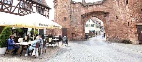 Das Jerusalemer Tor in Büdingen. Davor stehen im Außenbereich einer Gastronomie Tische, an denen Menschen sitzen.