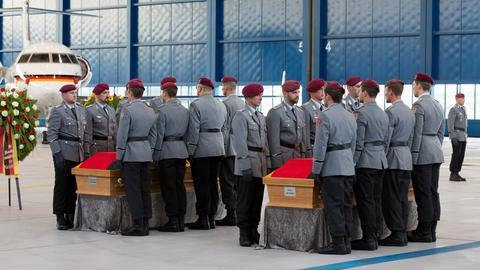 Soldaten neben den Särgen ihrer gestorbenen Kameraden.