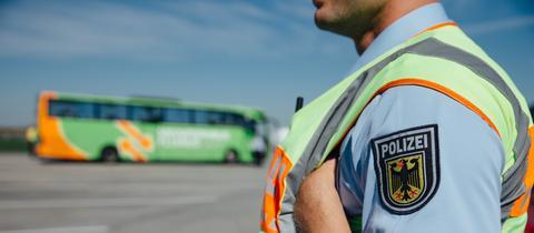 Ein Polizist, im Hintergrund ein Reisebus.