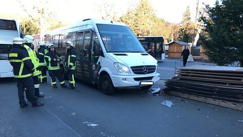 Feuerwehrmänner und der Bus, der links vorne beschädigt ist.