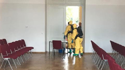 Feuerwehrmänner in Schutzanzügen stehen in einem Saal der Orangerie.