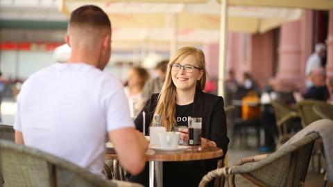Zwei junge Menschen sitzen draußen an einem Tisch eines Cafés