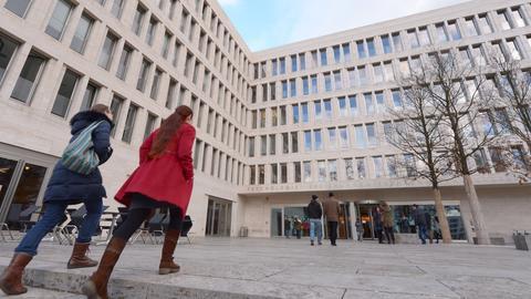 Zwei Studentinnen gehen auf dem Uni-Campus Westend in Frankfurt auf die Eingangstür des Uni-Gebäudes zu.