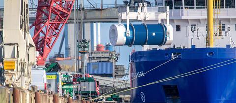 Castor-Behälter werden vom Schiff auf einen Zug geladen.