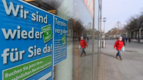 """Hinweiszettel """"Wir sind wieder für Sie da"""" und """"Terminvergabe"""" für das sogenannte """"Click & Meet"""" hängen an einem Schaufenster eines Schuhgeschäfts."""