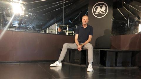 """Karl Börries sitzt auf der Tanzfläche seines """"Club 22""""."""