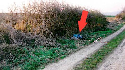 Foto eines Feldwegs in der Landschaft. Am Rand leicht verdeckt ein blauer Müllsack (in dem der Leichnam verborgen war). Ein roter Pfeil markiert in dem Bild die Stelle.