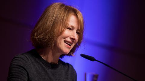 Eine Frau mit rotblonden Haaren steht an einem Mikrofon vor blauem Hintergrund