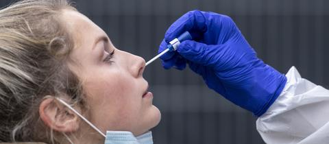 Eine Hand, bekleidet mit Schutzhandschuh, führt ein Teststäbchen in die Nase einer Frau ein.
