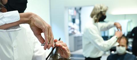 Ein Friseur mit Maske schneidet einem Kunden mit Maske die Haare.