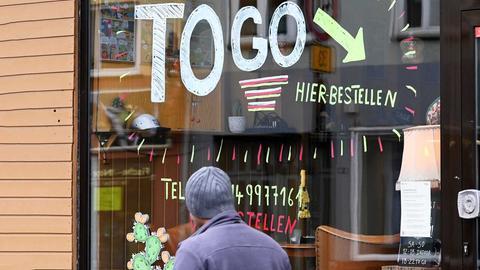 """An der Glasscheibe eines Cafés steht neben den verkürzten Öffnungszeiten die Stelle bezeichnet, an der man etwas """"to go"""" bestellen können."""