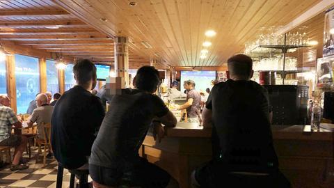 Besucher verfolgen in einer Bar eine Fußball-Übertragung